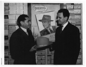 Photograph of Max Goldfine and Homer Stephenson holding a hat inside of Goldfine's department store. An advertisement for Resistol hats with a picture of Errol Flynn is on the wall behind them.