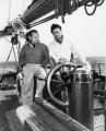 1US-764-F1946 (183165) Errol Flynn on his yacht / Photo Flynn, Errol US film actor, 1909-1959. - Errol Flynn at the helm of his yacht 'Zaca' (next to him Bill Keil, member of the ship's crew). - Photo, c.1946.