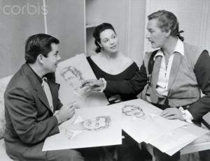 13 Jul 1952 --- Original caption: The Baroness Makes Up. Whims and whiskers are under discussion in this conference between Bud Westmore, (left), Mil Patrick, and Errol Flynn, the star for whom luscious Mil has sketched some beard styles. Her job of makeup designer is an important one on the lot. --- Image by © Bettmann/CORBIS