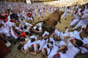 A cow jumping over revelers during the cow's festival at the swcond running of the bulls at the San Fermin Festival, in Pamplona, northern Spain, Friday, July 8, 2016. Revelers from around the world arrive to Pamplona every year to take part in some of the eight days of the running of the bulls. (AP Photo/Alvaro Barrientos)
